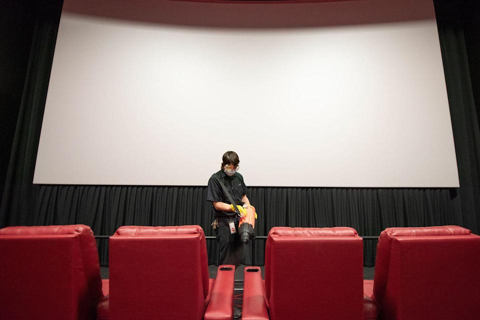 <p>An employee cleans a the theater with an electrostatic disinfectant spray machine at the AMC Highlands Ranch 24 on August 20 in Highlands Ranch, Colorado.</p>
