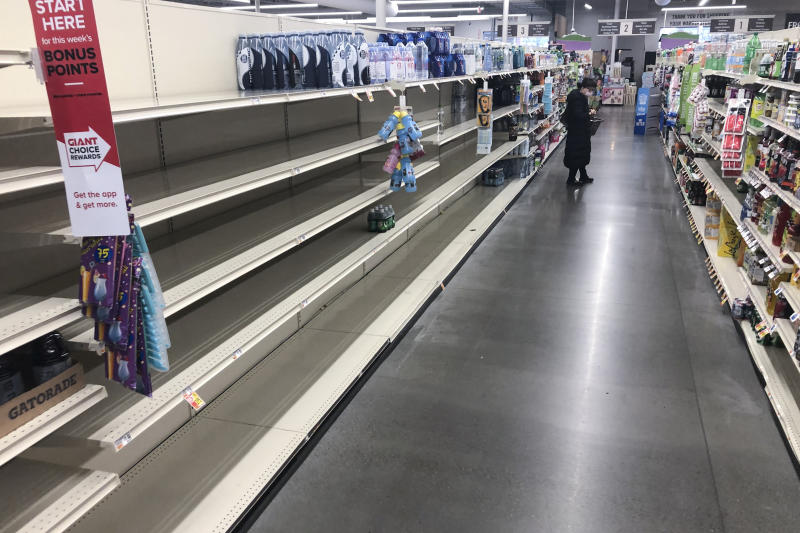 A shopper looks at items near empty shelves at a grocery store in Warrington, Pa., Tuesday, March 17, 2020. Coronavirus concerns have led to consumer panic buying of grocery staples.  (AP Photo/Matt Rourke)