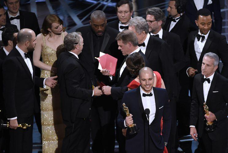 """Fred Berger, producer of """"La La Land,"""" foreground center, gives his acceptance speech as members of PricewaterhouseCoopers, Brian Cullinan, holding red envelope, and Martha L. Ruiz, in red dress, and a stage manager discuss the best picture announcement error among the cast at the Oscars on Sunday, Feb. 26, 2017, at the Dolby Theatre in Los Angeles. The actual winner of best picture went to """"Moonlight."""" (Photo: Chris Pizzello/Invision/AP)<br>"""