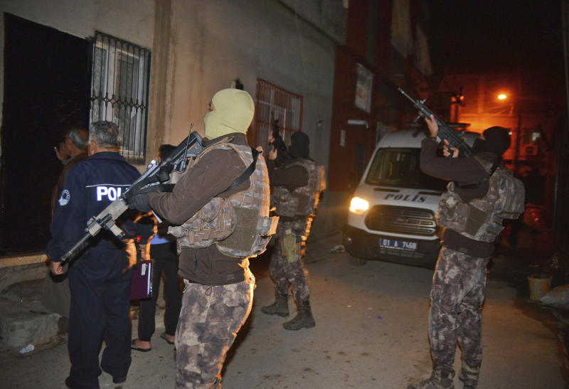 Masked Turkish police officers secure the perimeter outside a house during an operation to arrest people for alleged links to Islamic State group in Adana, Turkey, early Friday, Nov. 10, 2017. Turkey's official news agency reported 11 Syrian nationals were detained in the southern province of Adana for alleged links to IS group. (Gokhan Kesici/DHA-Depo Photos via AP)