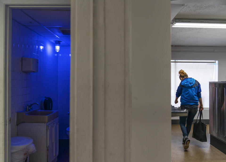"""A blue light illuminates the bathroom in the Cookie Carnival laundromat to make it harder for drug users to find a vein in Huntington, W.Va, Thursday, March 18, 2021. The laundromat was among several local businesses to install blue lights at the height of the city's opioid crisis, when they would often find syringes left behind by drug users. """"It was the only thing we could think of to do to help,"""" said manager Misti Mann-France. """"And it has helped tremendously."""" She said people have overdosed several times in the parking lot of their business. """"I wish there was a solution to the bigger problem,"""" she said. """"There are so many out there on drugs, and it's sad, it really is."""" (AP Photo/David Goldman)"""