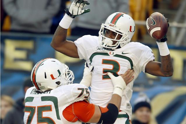 Miami wide receiver Stacy Coley (3) celebrates with offensive linesman Jared Wheeler after Coley made his second touchdown catch and run in the first quarter of an NCAA college football game against Pittsburgh in Pittsburgh on Friday, Nov. 29, 2013. (AP Photo/Keith Srakocic)