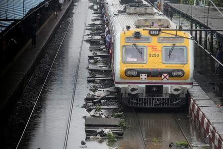 A passenger train moves through a water-logged track during heavy rains in Mumbai