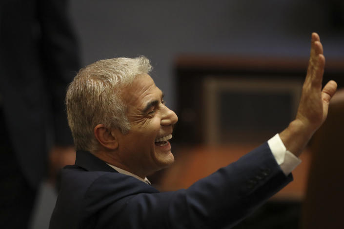 Israeli politician Yair Lapid of the Yesh Atid party sends greetings during a Knesset session in Jerusalem Sunday, June 13, 2021. Bennett is expected later Sunday to be sworn in as the country's new prime minister, ending Prime Minister Benjamin Netanyahu's 12-year rule. (AP Photo/Ariel Schali22