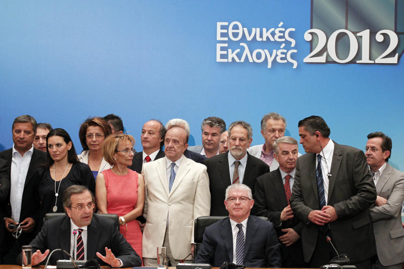 """Leader of the New Democracy conservative party Antonis Samaras, bottom left, speaks during a press conference in Athens, Sunday, June 17, 2012, as on the background reads """" national elections 2012''. The pro-bailout New Democracy party came in first Sunday in Greece's national election, and its leader has proposed forming a pro-euro coalition government.(AP Photo/Petros Giannakouris)"""