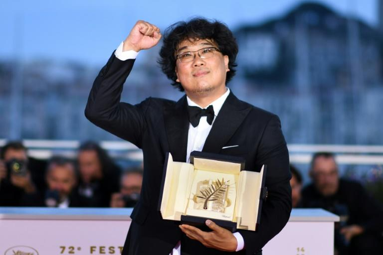 """South Korean director Bong Joon-Ho celebrates after he won the Palme d'Or at the Cannes Film Festival for """"Parasite"""" in May 2019"""