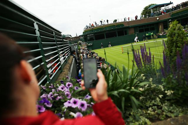LONDON, ENGLAND - JUNE 24: A sepctator uses her smartphone as she watches the action on an outside court during day one of the Wimbledon Lawn Tennis Championships at the All England Lawn Tennis and Croquet Club on June 24, 2013 in London, England. (Photo by Dan Kitwood/Getty Images)