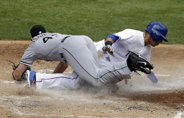 Chicago White Sox starting pitcher Erik Johnson (45) lands on top of Texas Rangers' Leonys Martin after tagging him out at home plate in the third inning of a baseball game, Sunday, April 20, 2014, in Arlington, Texas. Martin was trying to score from third on a wild pitch by Johnson during an Elvis Andrus at bat. (AP Photo/Tony Gutierrez)