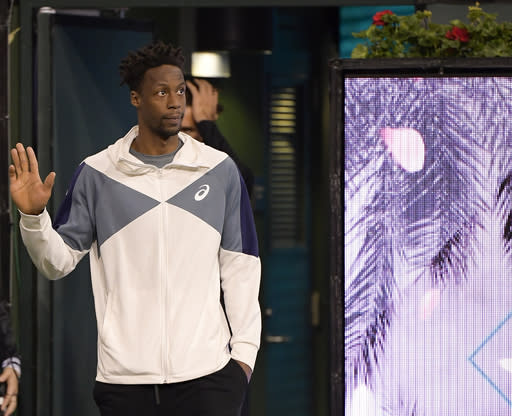 Gael Monfils, of France, waves to the crowd before being interviewed by tournament announcer Andrew Krasny at the BNP Paribas Open tennis tournament Thursday, March 14, 2019, in Indian Wells, Calif. Monfils announced on court that he could not play because of a left Achilles injury. (AP Photo/Mark J. Terrill)