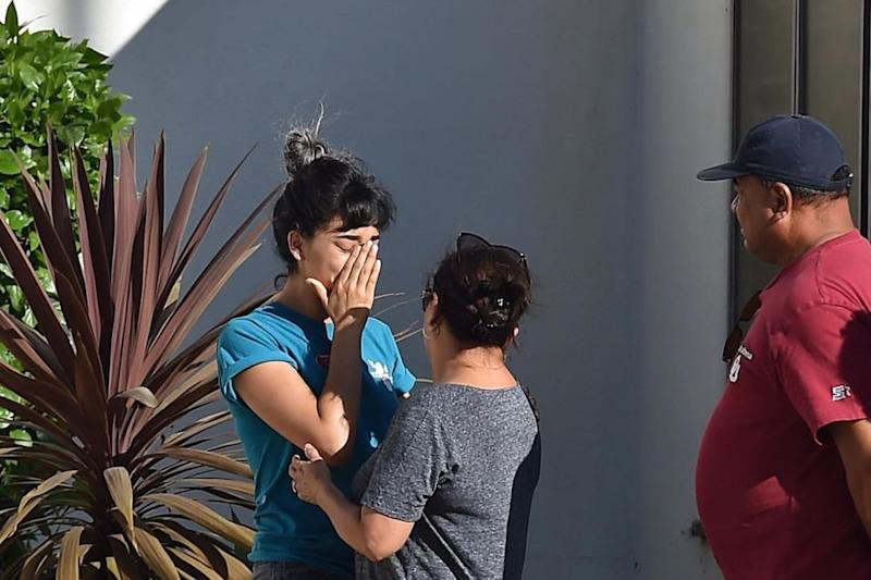 A Trader Joe's employee is comforted after what police described as a hostage situation at the grocery chain's location in L.A.'s Silver Lake neighborhood on Saturday.