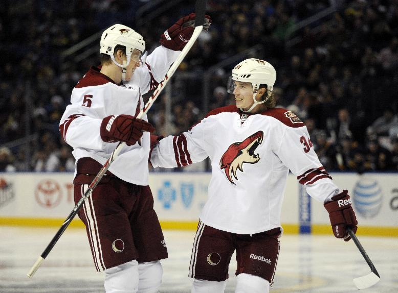 Phoenix Coyotes defenseman Connor Murphy (5) and left winger Tim Kennedy (34) celebrate a goal by Martin Hanzal during the second period of an NHL hockey game against the Buffalo Sabres in Buffalo, N.Y., Monday, Dec. 23, 2013. (AP Photo/Gary Wiepert)