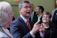 U.S. Department of Health and Human Services (HHS) Secretary Xavier Becerra, center, talks with with Oklahoma Medicaid advocates following a news conference Thursday, July 1, 2021, in Tulsa, Okla., as Oklahoma expands its Medicaid program. (AP Photo/Sue Ogrocki)
