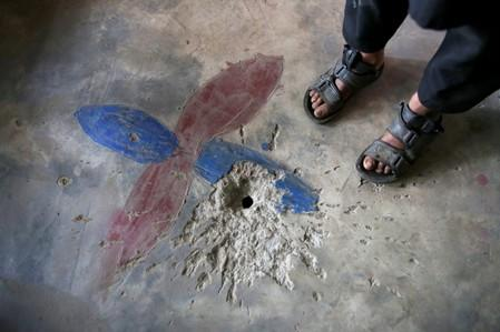 A boy stands next to a crater on the floor of his house, caused by a cluster bomb that according to family looked like a toy and exploded in the hands of a child, in village Jabri, in Neelum Valley
