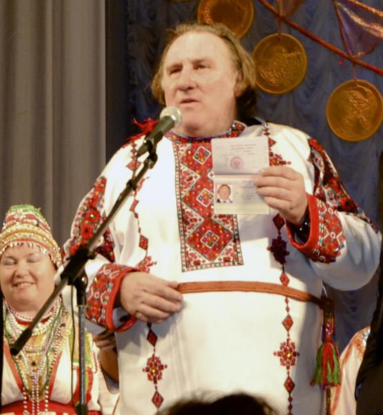 CORRECTING DATE TO SUNDAY JAN. 6 - French actor Gerard Depardieu poses with his new Russian passport on a theatre stage, wearing a traditional folk outfit, after he arrived in the city of Saransk, some 700 km (435 miles) east of Moscow, Russia, on Sunday, Jan. 6, 2013. Depardieu has received a Russian passport after flying to Russia for a late night dinner with Putin. Depardieu sought Russian citizenship as part of his battle against a proposed super tax on millionaires in France, and Putin granted his request last week. (AP Photo/Mordovmedia.ru)