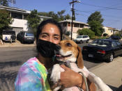 Briana Mendoza, 30, on Tuesday, Sept. 14, 2021, poses with her dog outside a polling site at a San Diego high school. Mendoza said she voted against recalling California Gov. Gavin Newsom. She said the state does not need to replace a governor who has been working to curb the spread of the coronavirus. (AP Photo by Julie Watson)