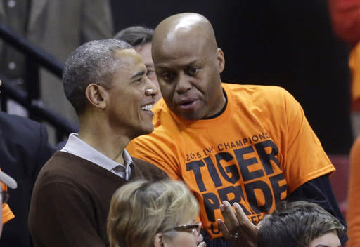President Barack Obama chats with his brother-in-law Craig Robinson before an NCAA college basketball game between Princeton and Green Bay in the first round of the NCAA tournament, Saturday, March 21, 2015, in College Park, Md. Robinson's daughter is Princeton forward Leslie Robinson. (AP Photo/Patrick Semansky)