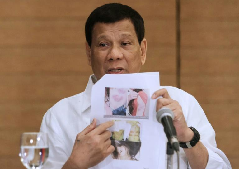 """Philippine President Rodrigo Duterte shows a photo of a Filipina worker in Kuwait, whom he said had been """"roasted like a pig"""", during a press conference in Davao City, in the southern island of Mindanao on February 9, 2018"""
