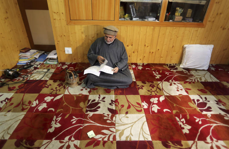 """In this Nov. 16, 2019 photo, Sheikh Showkat, a professor of international law and human rights at the central university of Kashmir reads a book inside his home in Srinagar, Indian controlled Kashmir. Many Kashmiri Muslims have for long said New Delhi curbs their religious freedom on the pretext of law and order while promoting and patronizing an annual Hindu pilgrimage to the Amarnath Shrine in an icy Himalayan cave visited by hundreds of thousands of Hindus from across India.""""The pilgrimage has seen a steady increase in its duration from 10 days to 45 days and number of devotees from some 15,000 before the start of the anti-India rebellion in 1989 to hundreds of thousands now,"""" said Prof. Sheikh Showkat. (AP Photo/Mukhtar Khan)"""