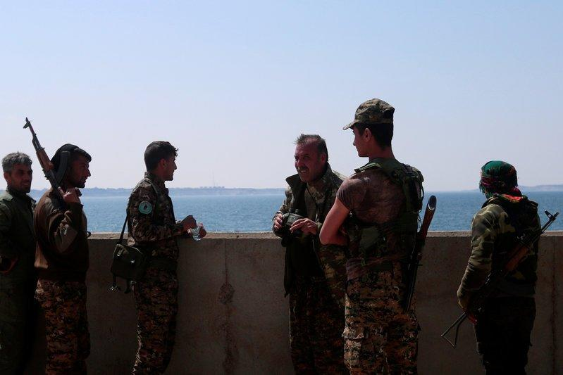 Syrian Democratic Forces (SDF) fighters stand at the northern part of the Tabqa Dam on the Euphrates River, Syria March 28, 2017. REUTERS/Rodi Said