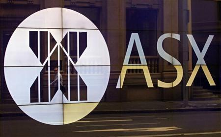 An office worker walks past the board of the Australian Securities Exchange building displaying its logo in central Sydney April 5, 2013. REUTERS/Daniel Munoz