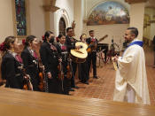 """After a long absence Tucson's St. Augustine Cathedral's rector, the Rev. Alan Valencia welcomes back the Mariachi band Los Changuitos Feos (Ugly Little Monkeys) as they prepare to preform during their morning Mass Sunday, Aug. 18, 2021 in downtown Tucson. """"Syncretism is the reality of this land, the 'ambos' reality,"""" says Valencia, the cathedral's rector, who grew up attending mariachi Mass in """"ambos Nogales,"""" or """"both Nogales,"""" as locals refer to the two cities of the same name straddling the U.S.-Mexican border about 60 miles (100 kilometers) to the south. (AP Photo/Darryl Webb)"""