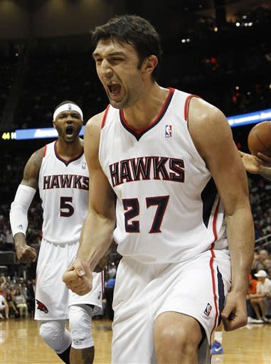 Atlanta Hawks center Zaza Pachulia (27) and Josh Smith (5) reacts after a basket in the second half of an NBA basketball game against the New York Knicks, Friday, March 30, 2012, in Atlanta. Atlanta won 100-90. (AP Photo/John Bazemore)