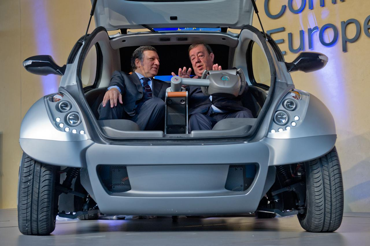 "BRUSSELS, BELGIUM - JANUARY 24:  EU Commission President Jose Manuel Barroso and Jesus Echave, chairman of the HIRIKO-AFYPAIDA corporate consortiumk, sit in the first prototype of the HIRIKO electric car, during the global launch of Hiriko Driving Mobility at the EU Commssion headquarters on January 24, 2012 in Brussels, Belgium. The electronic eco-friendly vehicle will be manufactured in deprived areas of cities who take up Hiriko's ""social purpose"" model. Malmo in Sweden has already signed up to trial Hiriko with Berlin, Barcelona, Vitoria-Gasteiz (the second largest Basque city), San Francisco, and Hong Kong expected to follow suit.  (Photo by Geert Vanden Wijngaert/Getty Images)"