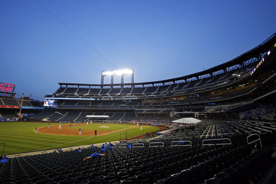 Players for the Mets are in the stands at an empty stadium with the field in front of them.