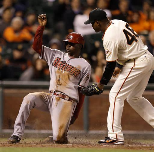 Arizona Diamondbacks' Didi Gregorius, left, scores past the tag of San Francisco Giants pitcher Santiago Casilla in the eleventh inning of a baseball game Tuesday, April 23, 2013, in San Francisco. Gregorious scored on a wild pitch from Casilla. (AP Photo/Ben Margot)