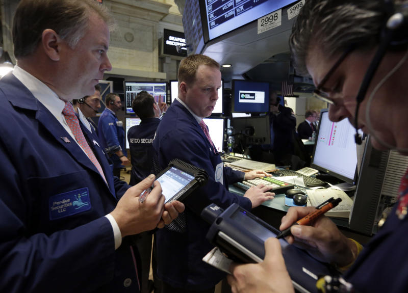 Traders gather at the post of Michael Smyth, center, on the floor of the New York Stock Exchange Tuesday, April 30, 2013. Stock prices are opening mostly lower on Wall Street as weak earnings from Pfizer and other companies drag down major market averages. (AP Photo/Richard Drew)