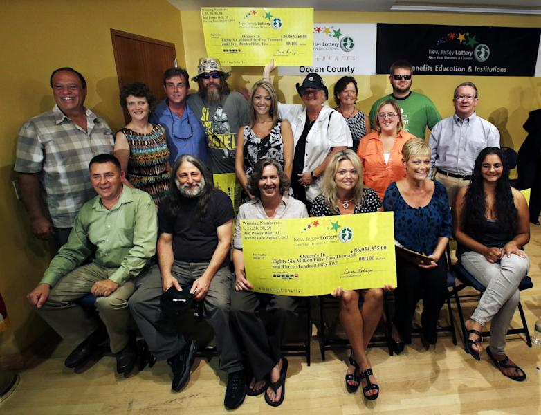 """Sixteen lottery winners pose for a photograph Tuesday, Aug. 13, 2013, in Toms River, N.J. The """"Ocean's 16,"""" as the group of Ocean County public employees, who work for work for the Vehicle Services department, on the Jersey shore has been dubbed after snagging one of three winning tickets in last week's $448 million Powerball jackpot, gathered Tuesday to discuss the windfall. The event comes one day after the nine women and seven men claimed their share of the jackpot. (AP Photo/Mel Evans)"""