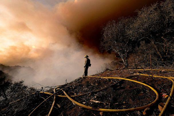 PHOTO: A firefighter keeps watch as smoke rises from a brush fire scorching at least 100 acres in the Pacific Palisades area of Los Angeles, May 15, 2021. (Ringo H.w. Chiu/AP)