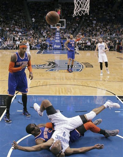 Orlando Magic's Arron Afflalo (4) lands on New York Knicks' Amare Stoudemire after being called with a charge while going up for a shot, as Knicks' Carmelo Anthony (7) watches during the first half of an NBA basketball game, Saturday, Jan. 5, 2013, in Orlando, Fla. (AP Photo/John Raoux)