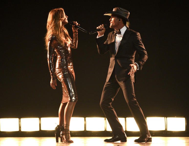 "FILE - In this April 2, 2017 photo, Faith Hill, left, and Tim McGraw perform ""Speak To A Girl"" at the 52nd annual Academy of Country Music Awards in Las Vegas. The country couple with movie star glamour has sold over 63 million albums in the U.S. between their two careers, has earned two Grammys for duets they sang together and has three children. This year, they are releasing their first-ever duet album together and started their third installment of their highly successful Soul2Soul World tour on April 7. (Photo by Chris Pizzello/Invision/AP, File)"