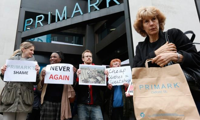 A shopper passes demonstrators outside clothing retailer Primark in central London on April 27.
