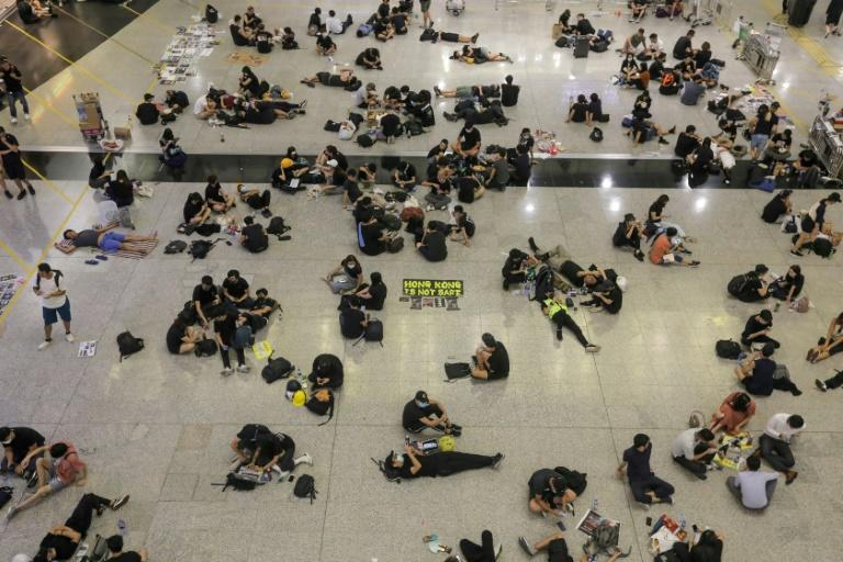 Protesters sit on the floor of the arrivals hall of Hong Kong's international airport during a protest which marked yet another dramatic escalation in a 10-week crisis