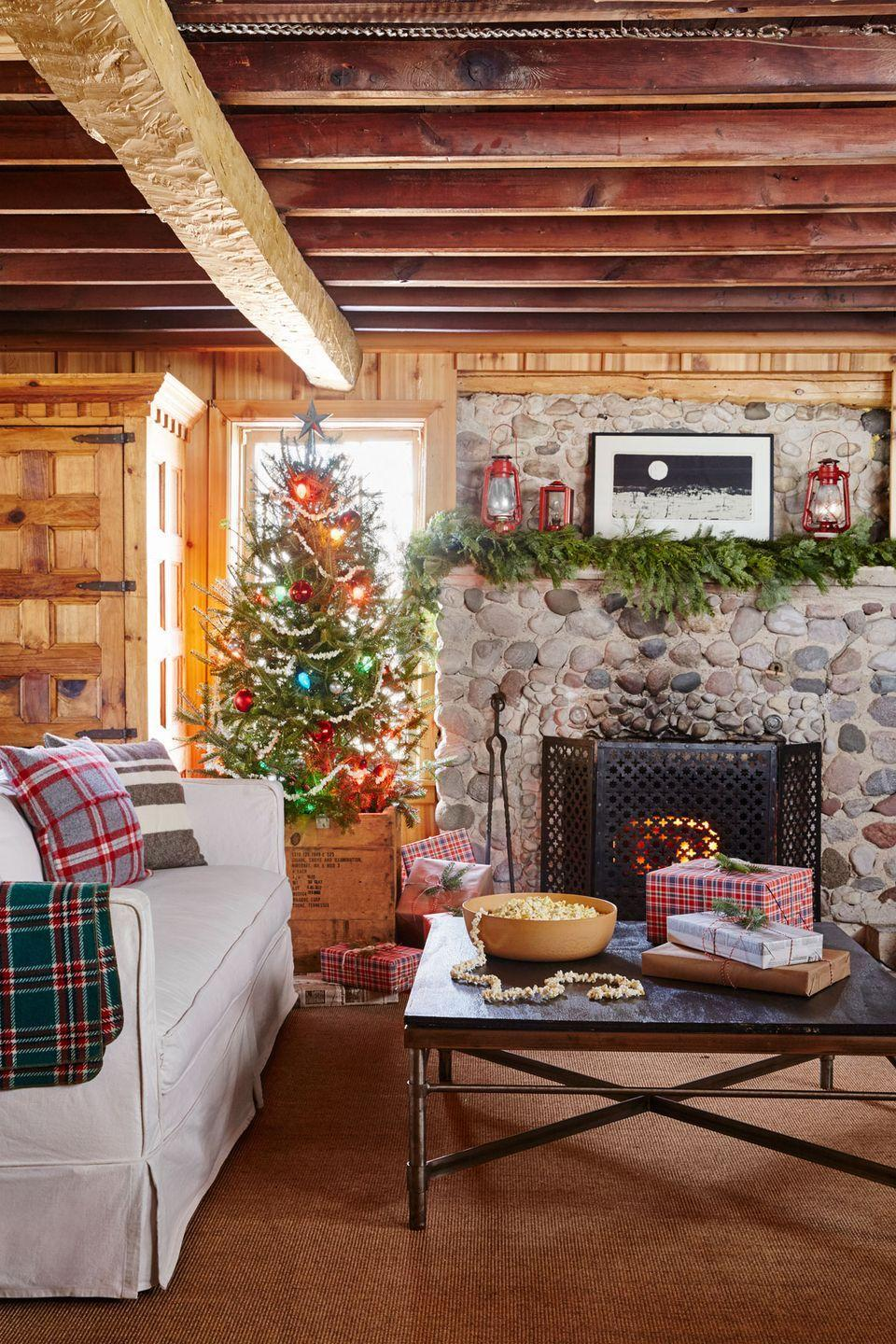 """<p>For the tree in this <a href=""""https://www.countryliving.com/home-design/house-tours/g2779/patrick-mcguire-cozy-christmas-cabin/"""" rel=""""nofollow noopener"""" target=""""_blank"""" data-ylk=""""slk:cozy Christmas cabin"""" class=""""link rapid-noclick-resp"""">cozy Christmas cabin</a>, a simple popcorn garland, glass ball ornaments, and a wooden crate in lieu of a tree skirt reinforce the home's-stuck-in-time vibe. The fir garland above the mantel and solo sprigs of pine found in vases throughout the house also add an organic element.</p><p><a class=""""link rapid-noclick-resp"""" href=""""https://go.redirectingat.com?id=74968X1596630&url=https%3A%2F%2Fwww.etsy.com%2Fmarket%2Fwooden_crates&sref=https%3A%2F%2Fwww.countryliving.com%2Fhome-design%2Fdecorating-ideas%2Fadvice%2Fg1247%2Fholiday-decorating-1208%2F"""" rel=""""nofollow noopener"""" target=""""_blank"""" data-ylk=""""slk:SHOP WOODEN CRATES"""">SHOP WOODEN CRATES</a></p>"""