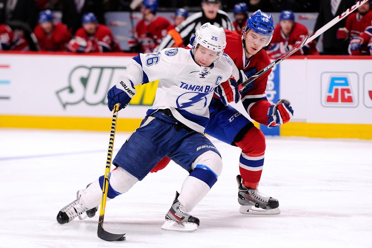 MONTREAL, QC - FEBRUARY 1: Martin St. Louis #26 of the Tampa Bay Lightning skates with the puck while being defended by Nathan Beaulieu #40 of the Montreal Canadiens during the NHL game at the Bell Centre on Febraury 1, 2014 in Montreal, Quebec, Canada. The Lightning defeated the Canadiens 2-1 in overtime. (Photo by Richard Wolowicz/Getty Images)