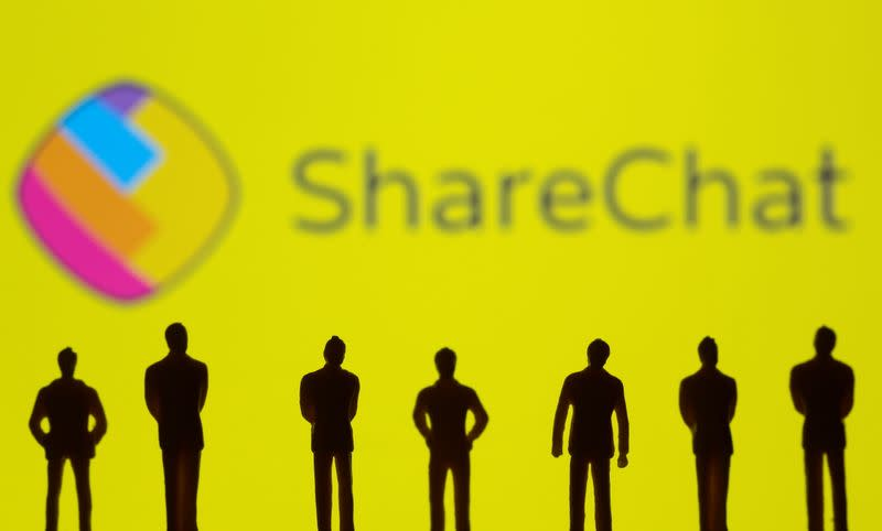 Small toy figures are seen in front of displayed ShareChat logo in this illustration taken