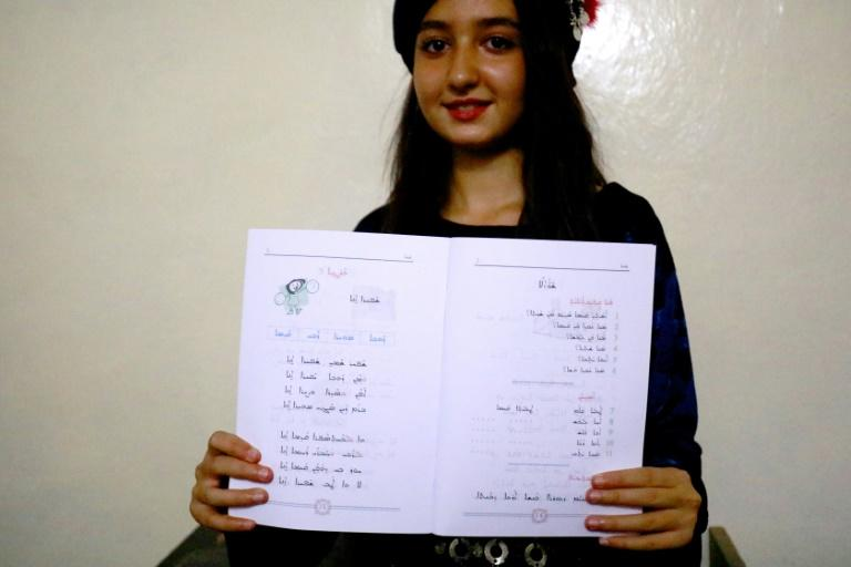 A student from the Syriac Christian minority shows a textbook in her language