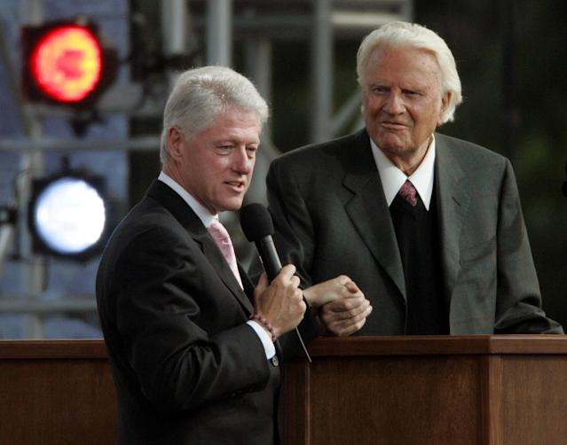 <p>Former president Bill Clinton, left, speaks alongside the Rev. Billy Graham on the second night of the Greater New York Billy Graham Crusade, June 25, 2005, at Flushing Meadows' Corona Park in the New York borough of Queens. (Photo: Frank Franklin II/AP) </p>