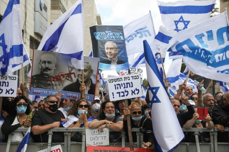 Israeli supporters hold flags and a poster depicting Prime Minister Benjamin Netanyahu alongside French officer Alfred Dreyfus, who was unjustly convicted of treason in 1895, during a rally outside the district court of Jerusalem (AFP Photo/Menahem KAHANA)