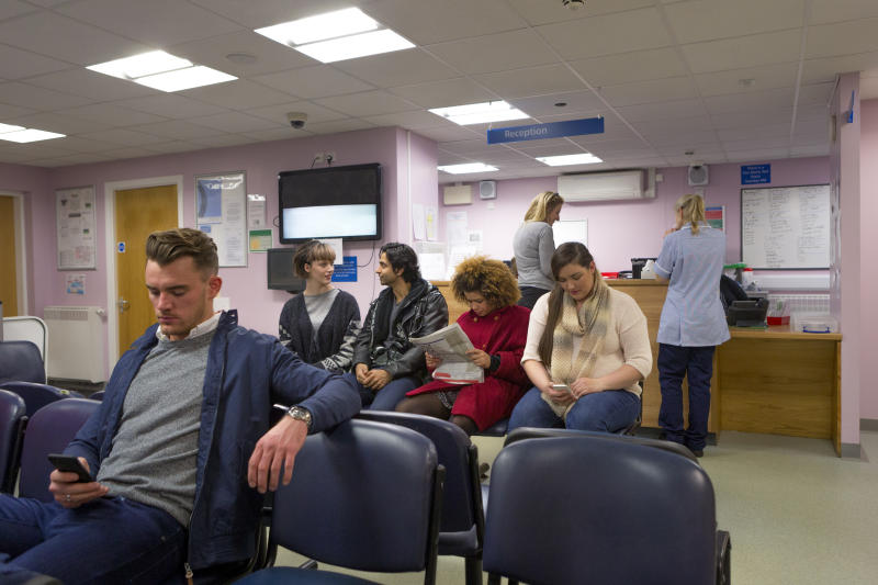A group of people can be seen waiting in a health clinic to be seen by the doctor. Government-run health care gives doctors minimal incentive to reduce patient wait times.
