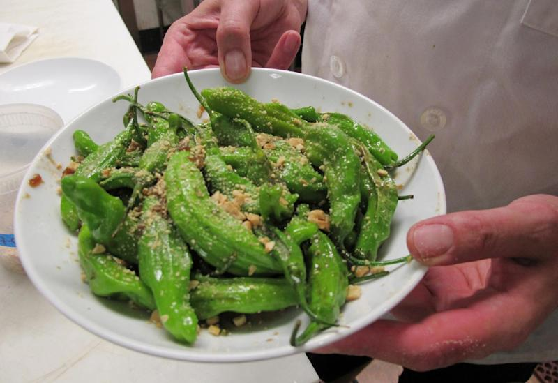 In this July 12, 2012 photo, chef Dan Jacobs holds a plate of shishito peppers at Roots Restaurant and Cellar in Milwaukee. The recent heat wave and drought across the upper Midwest have taken a toll on some crops, but Jacobs has noticed the weather has helped make some peppers extra-spicy. Jacobs says some jalapeño peppers have become so powerful that he has to be careful how he serves them. (AP Photo/Dinesh Ramde)