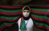 An Afghan refugee wearing a scarf in the colours of the national flag of Afghanistan participates in a protest outside the UNHCR office (United Nation High Commissioner for Refugees) in New Delhi, India, Monday, Aug. 23, 2021. Hundreds of Afghans living in India gathered to protest against the Taliban takeover of Afghanistan and also demanded to be given refugee status in India. (AP Photo/Manish Swarup)