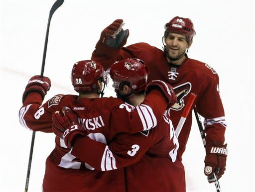 Phoenix Coyotes center Boyd Gordon (15) and Keith Yandle (3) celebrate with Lauri Korpikoski (28) of Finland, after Korpikkoski scored a second-period goal against the Anaheim Ducks during an NHL hockey game Saturday, March 2, 2013, in Glendale, Ariz. (AP Photo/Rick Scuteri)
