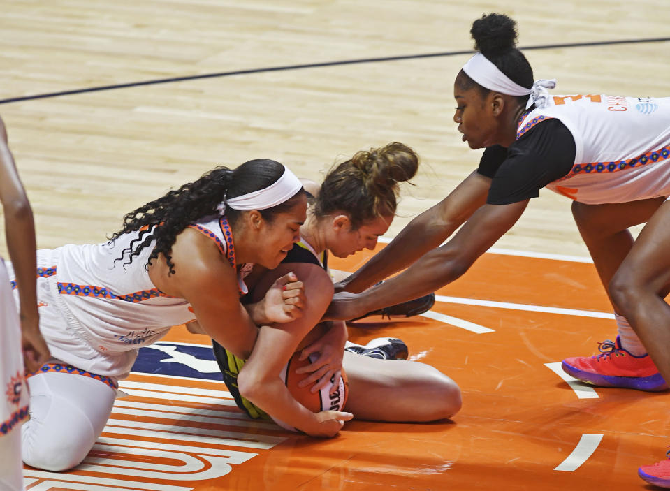 Connecticut Sun center Brionna Jones, left, and forward Kaila Charles wrap-up Dallas Wings guard Marina Mabrey during a WNBA basketball game Tuesday, June 22, 2021 at Mohegan Sun Arena in Uncasville, Conn. (Sean D. Elliot/The Day via AP)