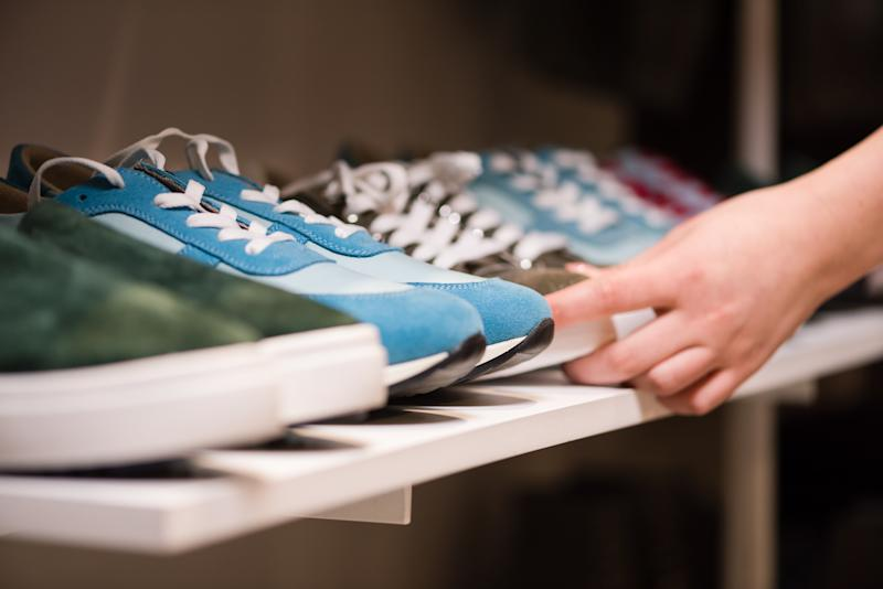 Close-up of female hands putting sneakers suede shoes collection on store rack. Consultant arrange colorful new shoes for sale at boutique mall.