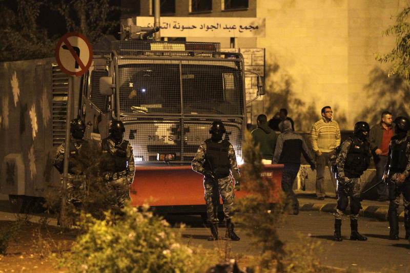 In this photo taken late Tuesday, Nov. 13, 2012, Jordanian policemen stand guard as protesters take part in a demonstration following an announcement that Jordan would raise fuel prices, including a hike on cooking gas, in Amman, Jordan. Police say hundreds of Jordanians have poured into the streets of several cities for a second day to protest a government decision to lift fuel subsidies and raise prices.(AP Photo/Raad Adayleh)