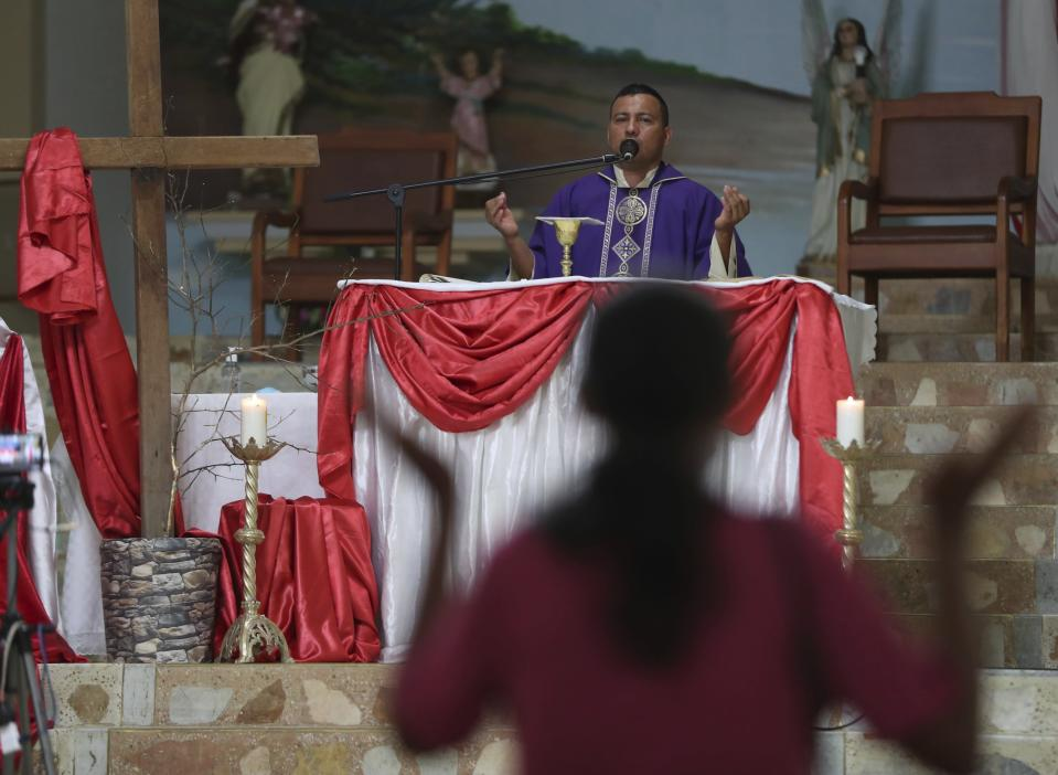 Father Camilo Monrroy celebrates Mass in Campohermoso, Colombia, Thursday, March 18, 2021, amid the new coronavirus pandemic. Father Monrroy says that constant prayer by the town's citizens, especially to St. Roque, patron saint of the parish, the sick and epidemics, has made St. Roque the patron saint of COVID in the department of Boyaca. (AP Photo/Fernando Vergara)